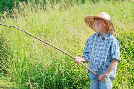 carex: Angler concentrated boy is watching after handmade fishing rod float on water Stock Photo