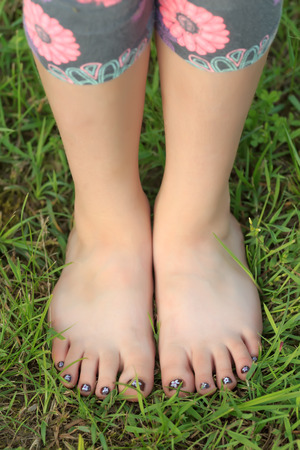 Close-up view of little shoeless girl toes on feet at green grass background Foto de archivo