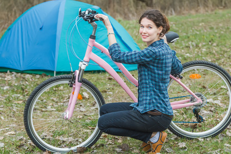 pink bike: Brunette girl sitting near pink bike during her bicycle touring