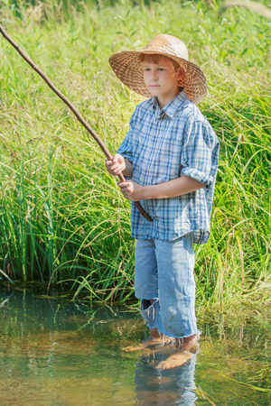 shoeless: Barefoot angler boy is fishing standing in transparent freshwater pond