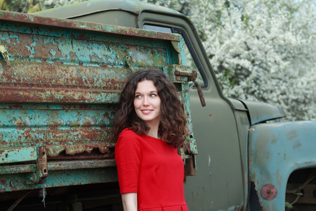 leaning on the truck: Blue-eyed brunette standing near truck body with peeling robin egg blue and green color paint