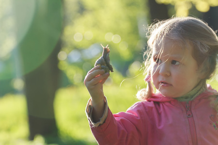 recreational area: Three years old preschooler girl with short pigtails is holding edible snail Stock Photo