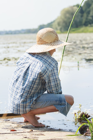 shoeless: Sitting on wooden bridge shoeless young fisherman with fishing rod Stock Photo