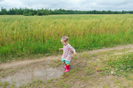 Blonde curly preschooler girl is playing on farm dirt road near puddle