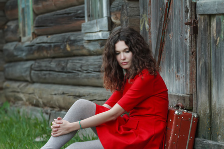 log house: Portrait of young woman is sitting in front of old log house with vintage suitcase Stock Photo