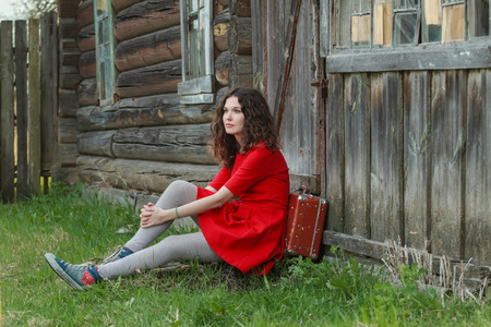 log house: Young woman is sitting on threshold of old log house with vintage suitcase
