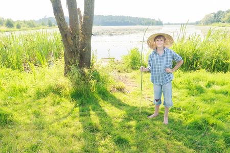 shoeless: Cheerful angling teenage boy with handmade green twig fishing rod in his hand