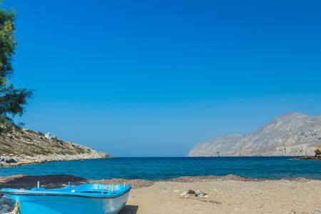emborio: Azure fishermans boat and sea horizon line on Alexi or Alexis wild natural beach near Emborios Greek village on Kalymnos island