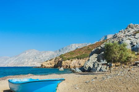 emborio: Blue fishermans boat and evergreen tamarisks on Alexi or Alexis wild natural beach near Emborios Greek village on Kalymnos island