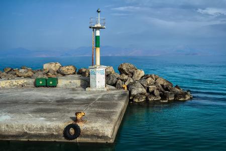 berth: Old concrete Mastihari berth on Greek Kos island with pier lighthouse