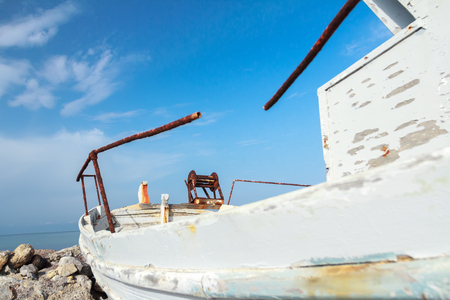 transom: Profile view of obsolete wooden fishing boat with peeling white paint on Greek Kos island