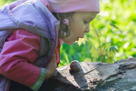 Three years old preschooler girl is blowing on crawling edible snail