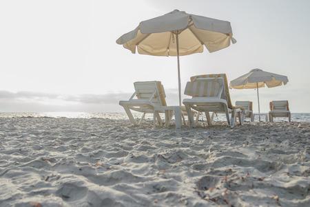 sunbeds: Sunset sandy beach on Greek Kos island with parasols and sunbeds