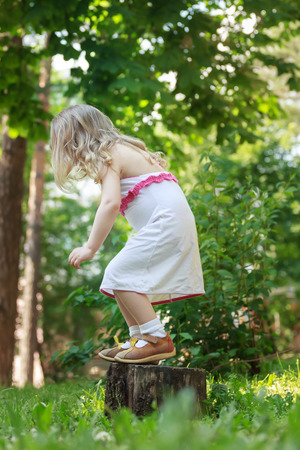 squatting down: Toddler girl is jumping down from tree stump back view