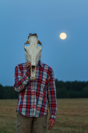 necromancy: Young man with horse skull on his head at night moonlight field