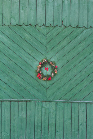 Christmas wreath from fir branches at green wooden door background Stock Photo