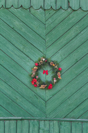 red christmas ball: Festive X-mas outside wreath is hanging on old rustic green door