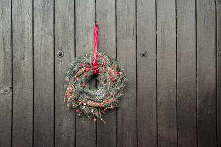 Christmas Holiday Advent wreath is hanging outside at brown wooden gates background