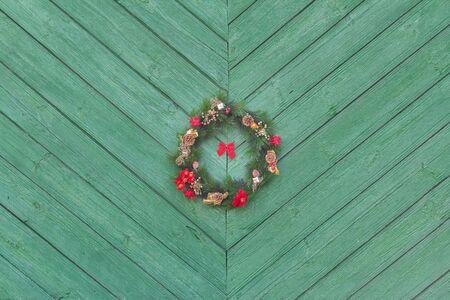 corona de adviento: Vacaciones de Navidad Corona de Adviento colgando fuera en verde puerta de madera con textura de fondo