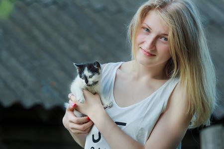 noir et blanc: Jeune fille de cheveux couleur paille tient petit chaton noir blanc sur les bras
