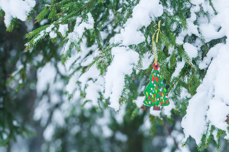 handmade wooden ornament of fully decorated christmas tree is hanging on snowy spruce twig stock photo