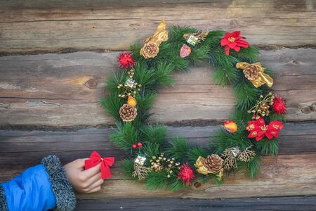 Girl hand is holding red bow and hanging on rustic log cabin wall with X-mas wreath