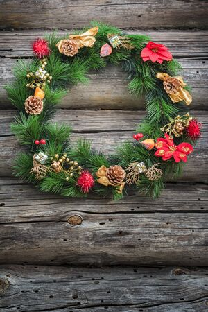 log cabin winter: Festive green winter Christmas wreath is at weathered log cabin wall background