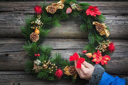 iglesia: el brazo de la muchacha con el azul de la manga de la chaqueta caliente es la decoraci�n festiva corona de Navidad