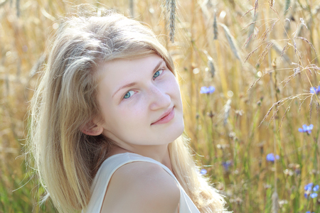 secale: Summer outdoor headshot portrait of blonde girl at grain ears field floral background