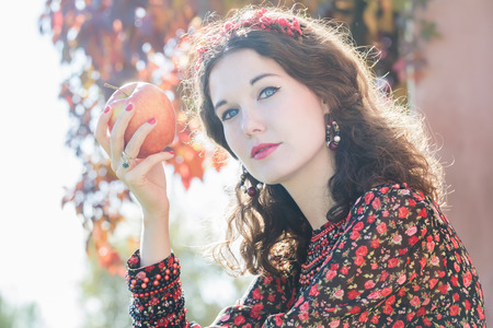 bead embroidery: Head and shoulders portrait of autumn girl in fall wreath with big ripe apple fruit in her hand