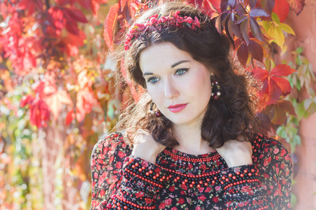 bead embroidery: Portrait of fairy autumn girl with red fall wreath at red floral background of grape woodbine Stock Photo