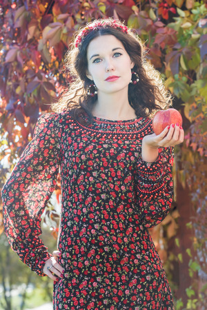 bead embroidery: Portrait of looking at camera autumn girl in fall head wreath with red apple in her arm Stock Photo