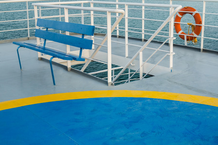upper floor: Empty upper deck with blue wooden bench and helicopter pickup point on Greek passenger sea ferry