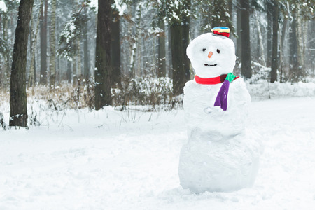 snowman wood: Holiday winter three snowball snowman with striped hat and scarf Stock Photo