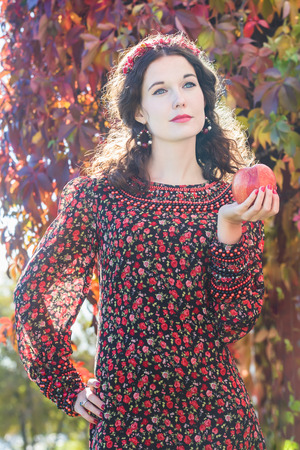 bead embroidery: Portrait of standing autumn girl in fall head wreath with red apple in her hand Stock Photo
