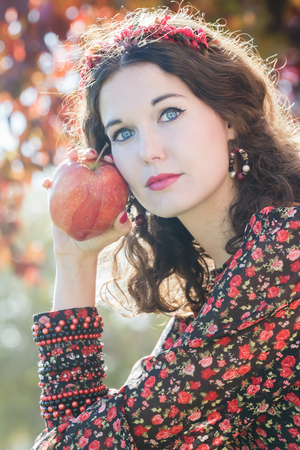 bead embroidery: Vertical shot of autumn girl in fall wreath with big ripe apple fruit  in her arm