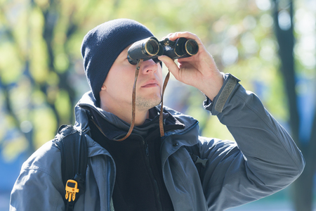 bird watching: Young man with binoculars is bird watching at demi-season natural background Stock Photo