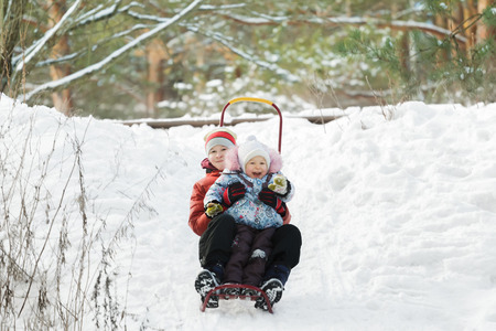 having fun in winter time: Sibling children are having fun sliding down snowy hill during winter time Stock Photo