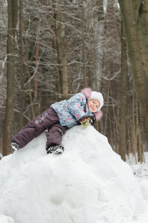 mignonne petite fille: Little girl is playing on snowy hill in beautiful winter park