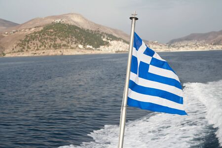 ultramarine blue: Greek national flag at sea waves and lonely island background Stock Photo