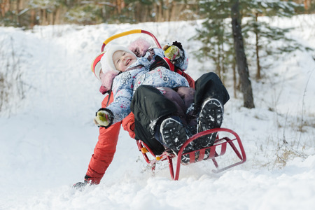 having fun in winter time: Excited sibling children are laughing during sledding down snowy hill by wooden sled Stock Photo