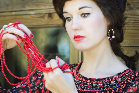 boyar: Russian beauty is looking on red round coral beads in her raised arms Stock Photo