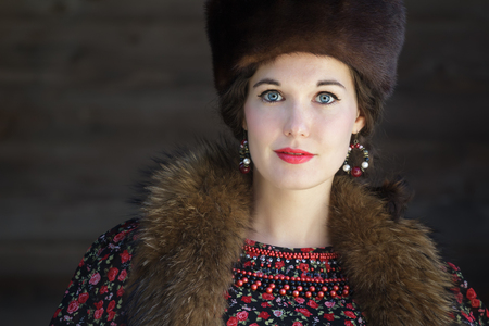 bead embroidery: Head and shoulders portrait of Russian beauty with blue eyes wearing dark fur Cossack hat Stock Photo