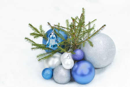 christmas ground: Young spruce tree on snowy ground with Christmas silver and blue ornaments at the bottom