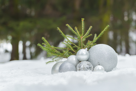 christmas ground: Small fir tree on snowy ground with Christmas bauble ornaments at the bottom