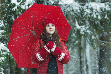 collapsible: Winter outdoors portrait of smiling young woman is holding fully collapsible umbrella in snowstorm