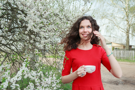 afternoon tea: Cheerful young lady in red dress and waving hair in windy spring blooming white fruit garden Stock Photo