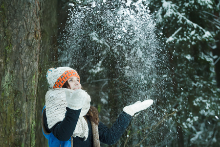 warmers: Cheerful girl is tossing up fresh snow in winter outdoors