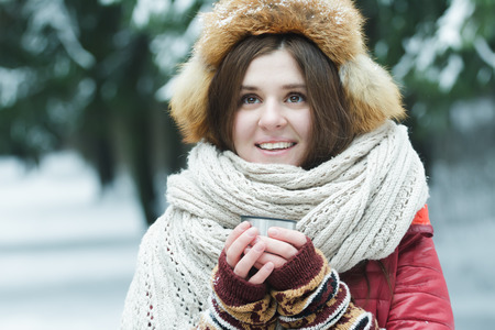 forest tea: Outdoor winter portrait of cheerful young lady is holding tourist vacuum flask cup with hot drink