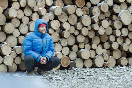 cuclillas: Cuclillas le�ador en el fondo de la le�a pila de iniciar sesi�n al aire libre en los bosques de abeto de monta�a de invierno